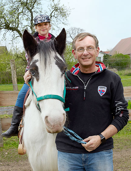 Bernd Siggelkow standing next to a horse a child is sitting on (Photo)